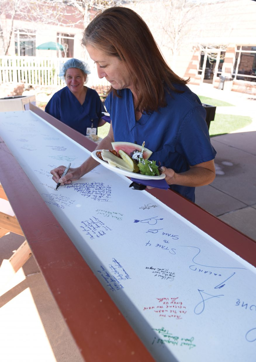 Laurel Lee Berry, a certified surgical tech at Yampa Valley Medical Center, signs a steel beam during an employee luncheon Thursday afternoon. The beam, which was signed by staff, volunteers, physicians and cancer survivors, will be placed in the new Jan Bishop Cancer Center during a topping out ceremony May 18.