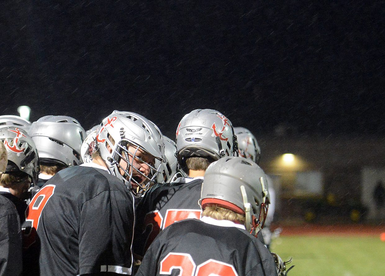 Steamboat's Logan Bankard looks to the scoreboard while huddling behind his teammates during a cold rainstorm Wednesday as the Sailors played in the lacrosse state semifinals.