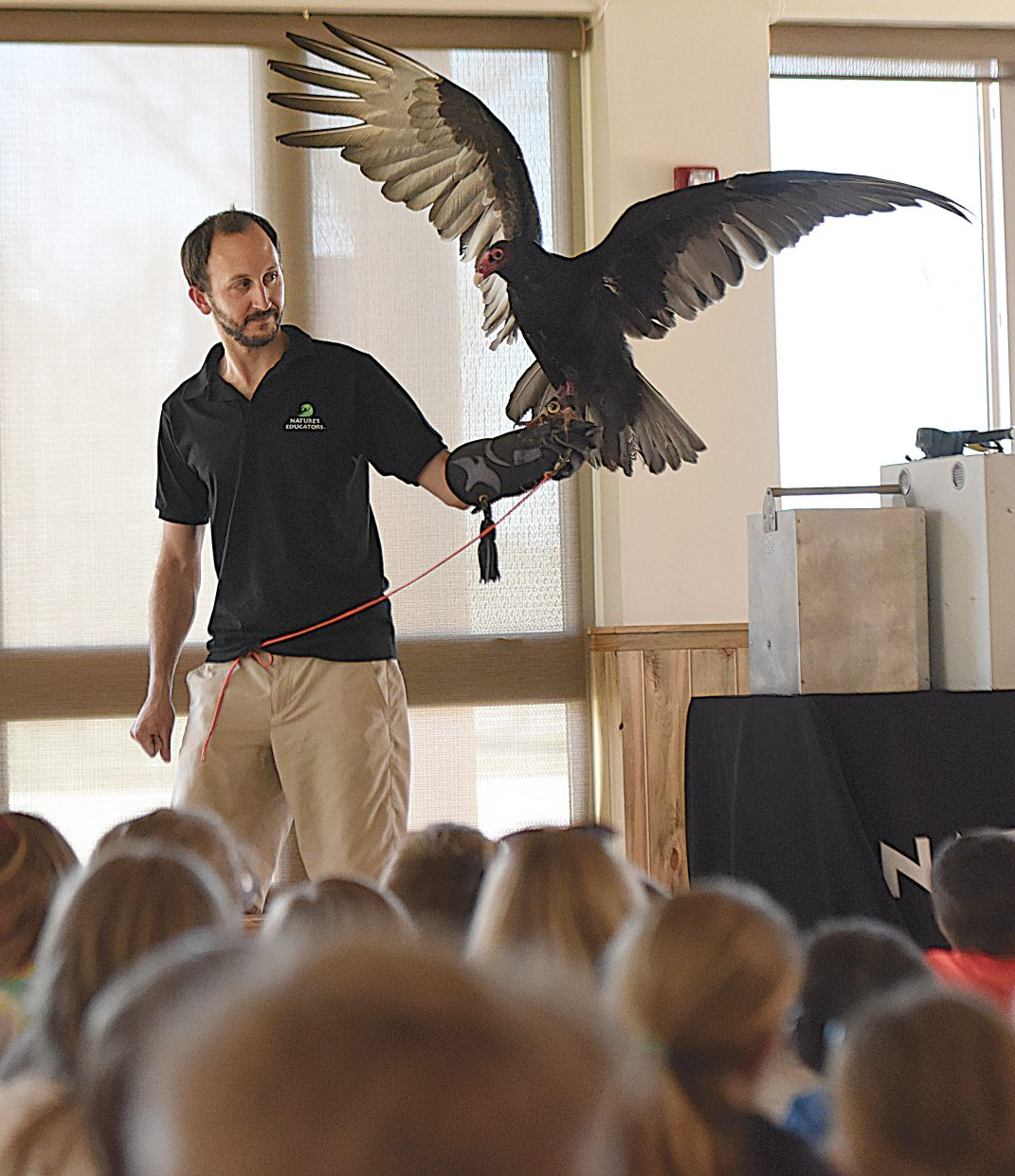 Evan Jaffe, a volunteer with Nature's Educators, holds a turkey vulture during a presentation at North Routt Community Charter School Friday morning. Nature's Educators also had presentations in Hayden and will be at the Bud Werner Memorial Library in Steamboat Springs from 9-10:30 a.m. today as part of Migratory Bird Day.