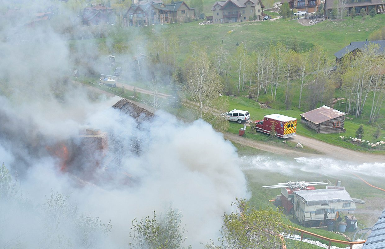 Smoke and flames pour out of a home on Apres Ski Way Thursday morning. The blaze destroyed the home.