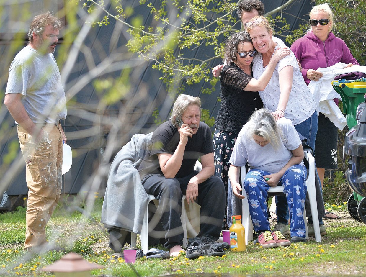 Neighbors comfort the owners of a home on Apres Ski Way while watching firefighters battle the blaze that destroyed the home Thursday morning in Steamboat Springs.