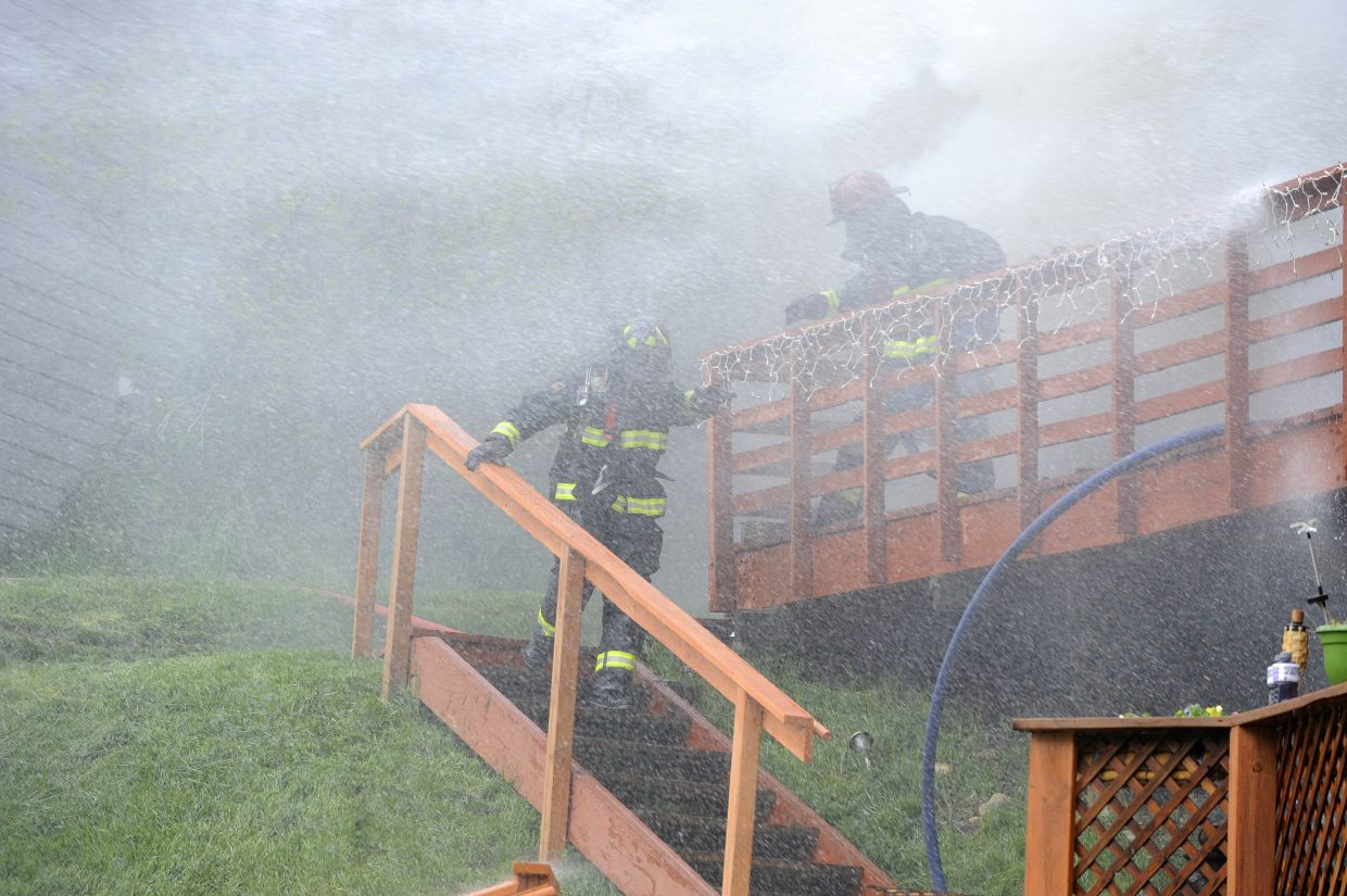 Firefighters walk down the steps of the burning home.