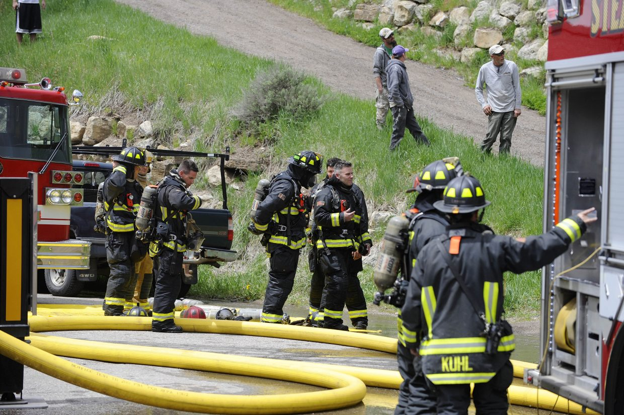 Firefighters gather on Après Ski Way, where a fire destroyed a home.