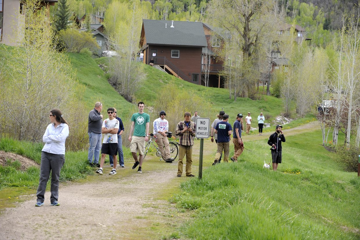 People gather on a trail to watch a home burn on Après Ski Way.
