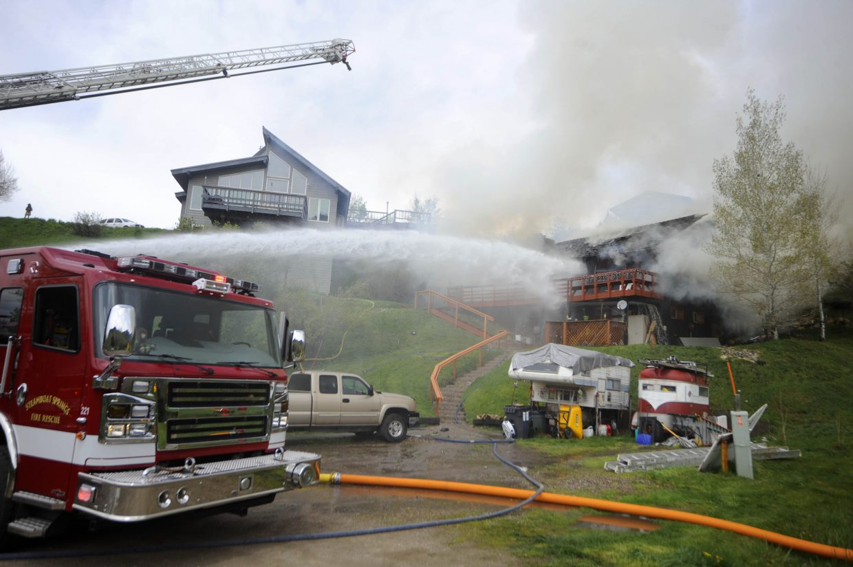 Firefighters work to put out a home on fire on Après Ski Way.