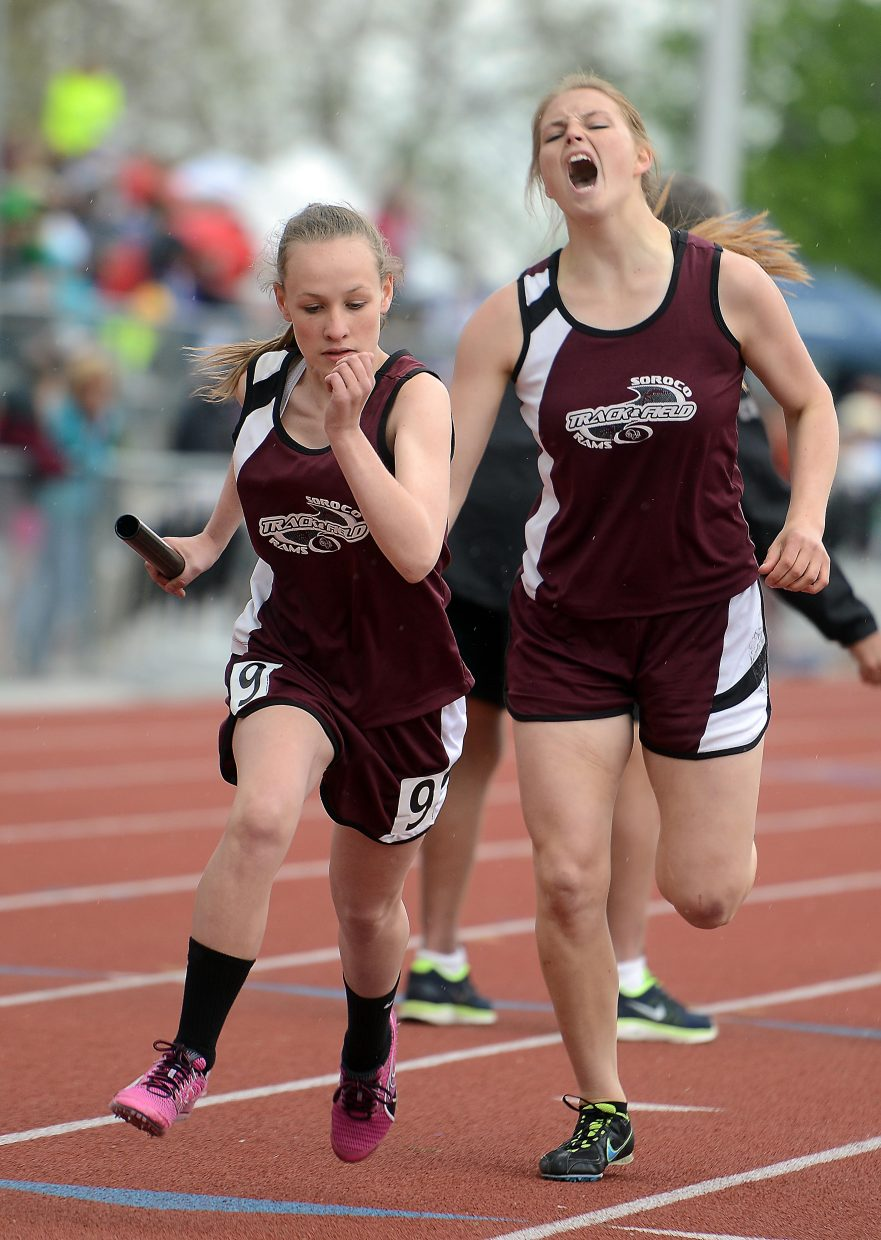 Cassie Constine takes off with the baton as Jessica Rossi cheers her on Friday during the 1,600-meter relay.