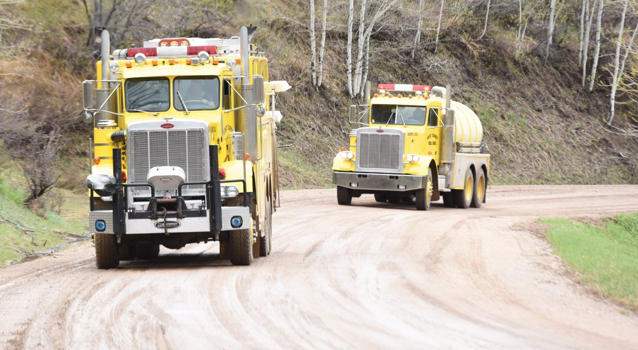 West Routt Fire Department fire trucks arrive near the scene of an oil well fire on private property at Wolf Mountain Ranch.