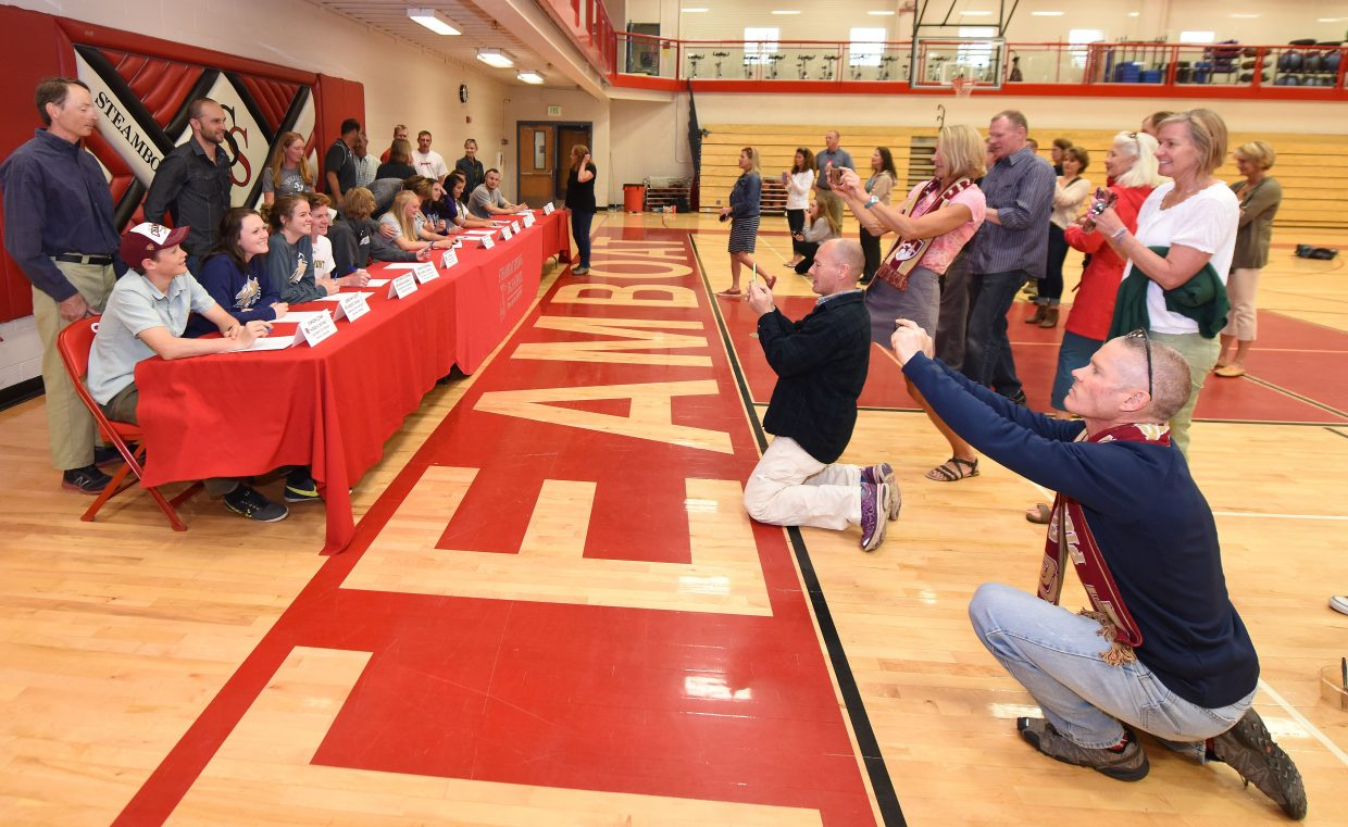 Parents crowd in for photos as 14 Steamboat Springs High School athletes are recognized for their achievements and their plans to compete next year at their chosen colleges.