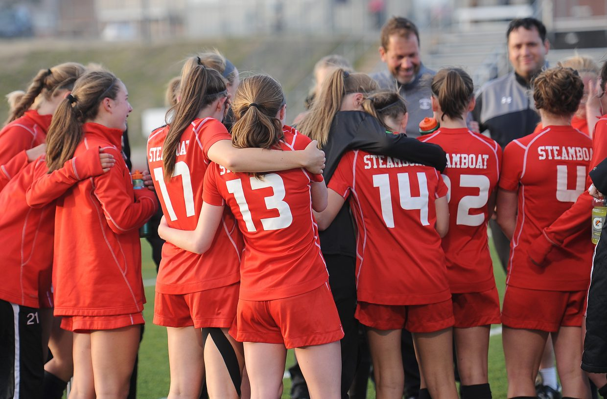Members of the Steamboat Springs High School girls soccer team share hugs as coach Rob Bohlmann addresses the team following Thursday's loss in the quarterfinal round of the state playoffs. The team finished the season 16-2.