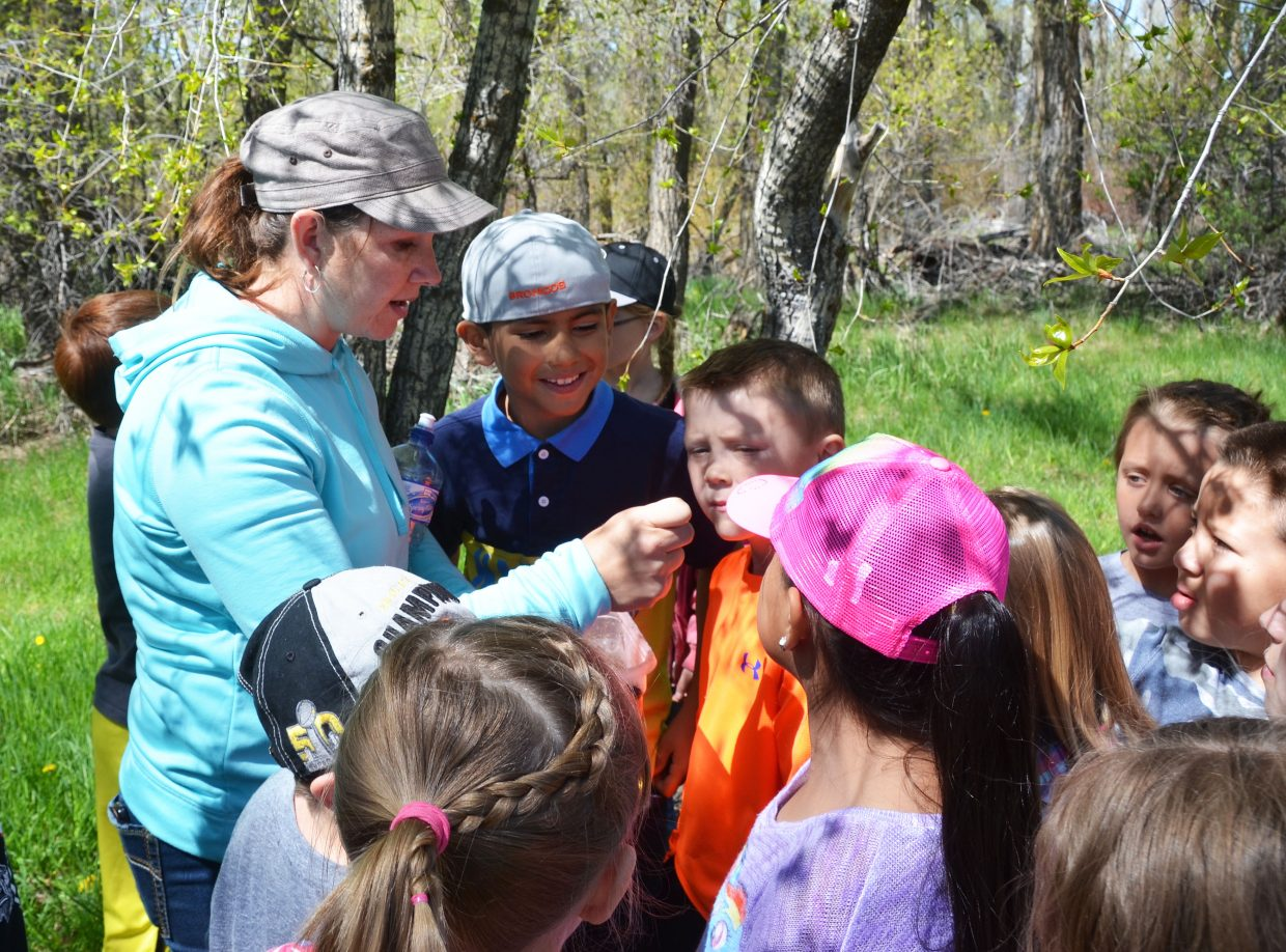 "Chris Rhyne, a range specialist with the Bureau of Land Management, shows a tiny rock to a group of Sandrock Elementary School third-graders at Yampa River State Park on Wednesday. ""We focused on the weathering and erosion (of rocks) because that's what's most common in our area,"" she said."