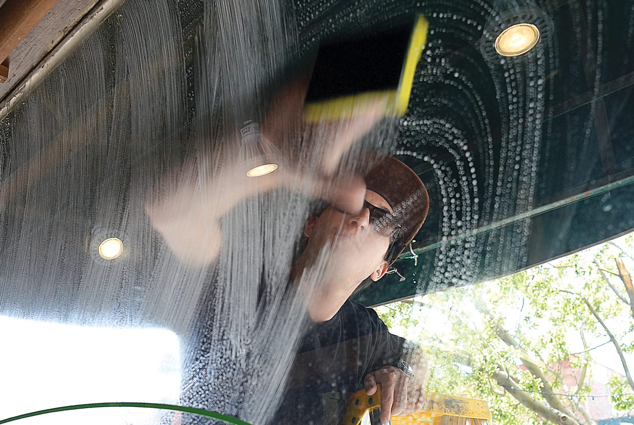 Teddy Heid washes windows at Straightline Outdoor Sports on Monday afternoon in downtown Steamboat Springs. With the Memorial Day holiday and the start of the summer season quickly approaching, it's time to do a little spring cleaning before the visitors begin arriving.