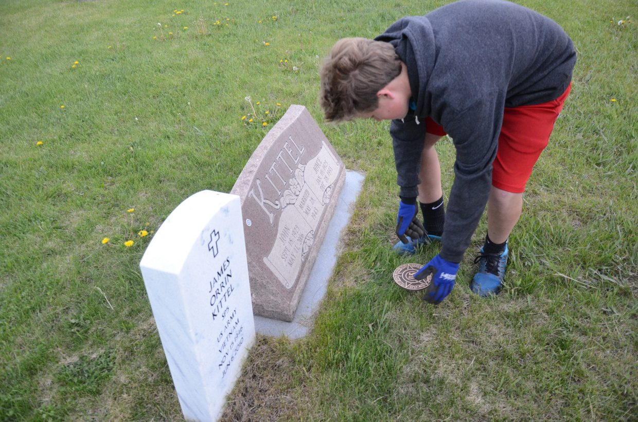 Rye Kirchner places a bronze marker in front of a veteran's grave at the Steamboat Springs Cemetery on Monday.