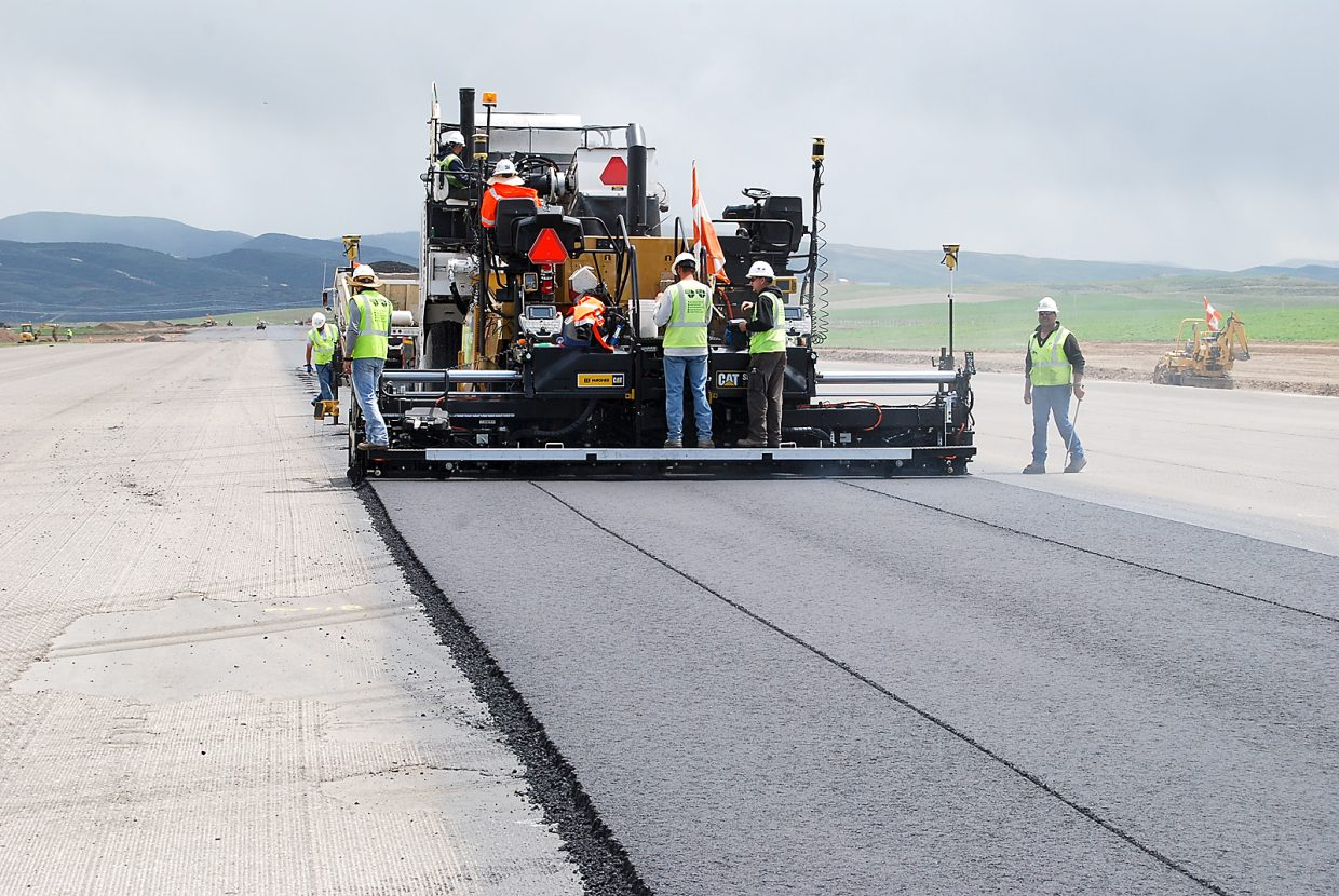 Crews from United Co. work on the first lane of asphalt in the re-paving of the runway at Yampa Valley Regional Airport with rain showers in the distance. An unsually wet month of May has delayed the paving work, but time remains to complete the job before the June 15 scheduled re-opening of the airport in Hayden.