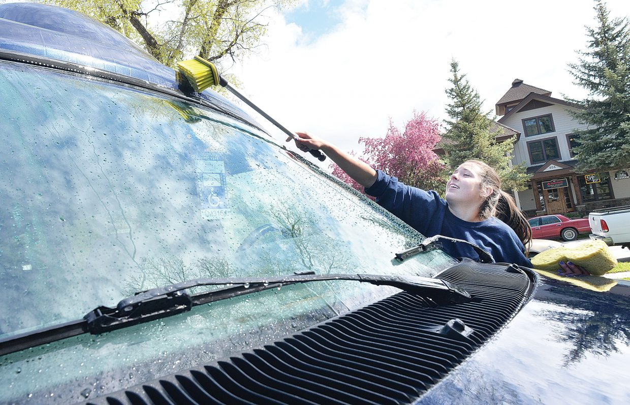 Steamboat Springs High School student Britteny Starks, a member of the National Honor Society, cleans vehicles at Horizons Wednesday. Starks and her classmates were taking part in the Routt County United Way's 2015 Day of Caring. Volunteers completed a number of different projects at sites around the community Wednesday in a showing of community spirit and caring.