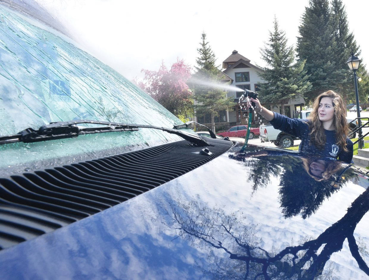 Steamboat Springs High School student Anna Skubiz, a member of the National Honor Society, cleans vehicles at Horizons Wednesday. Skubiz and her classmates were taking part in the Routt County United Way's 2015 Day of Caring. Volunteers completed a number of different projects at sites around the community Wednesday in a showing of community spirit and caring.