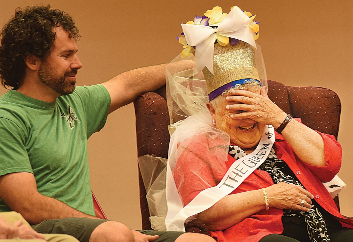 Longtime Steamboat Springs High School teacher Sandy Conlon, seated by her son, Fred, reacts during a retirement pep assembly Friday morning. Conlon, who has taught for 56 years including the past 46 in Steamboat Springs, was caught off guard by a school-wide assembly that included the entire student body, former students and her family members.