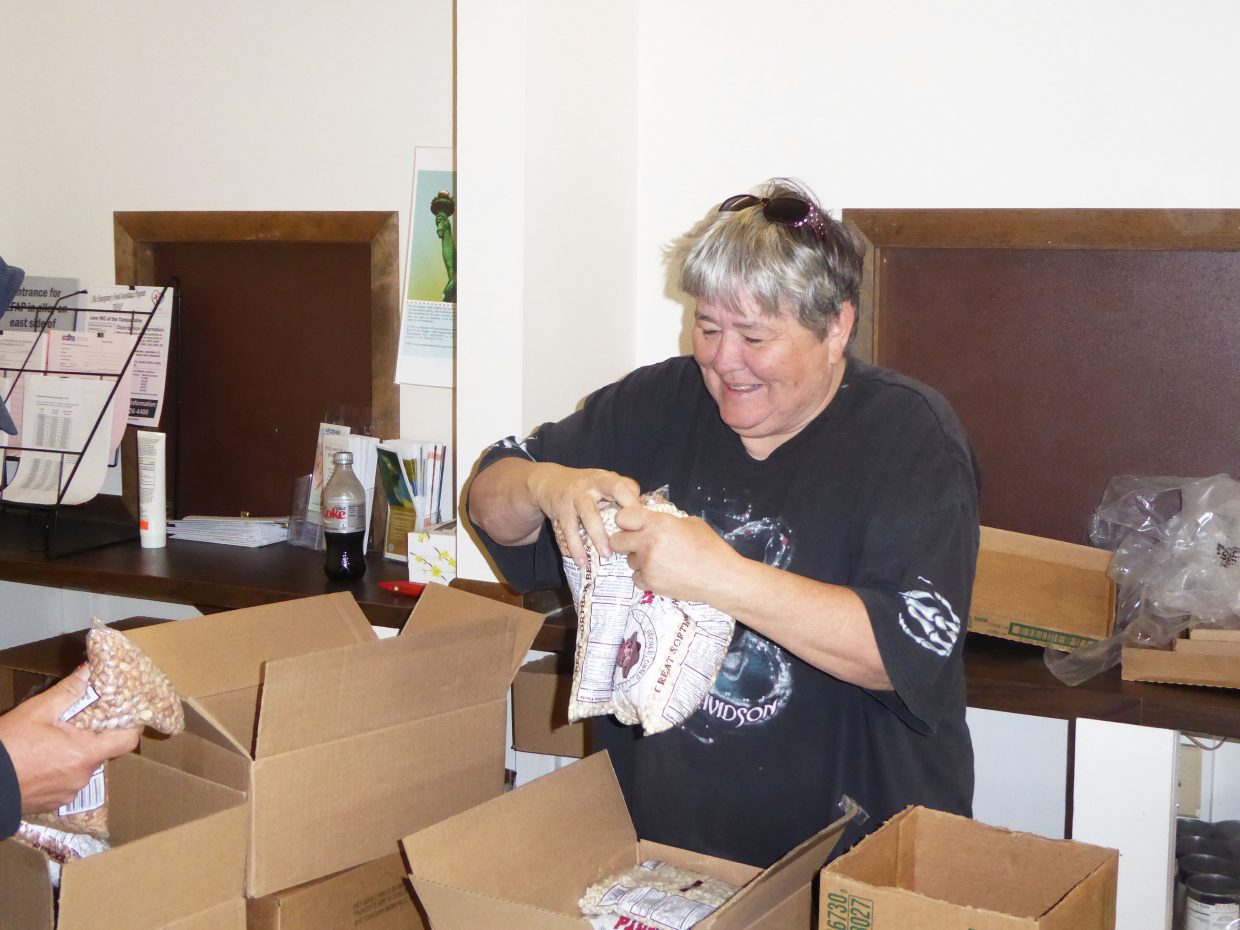 Pam Lathrop, volunteering for Love INC, talks and laughs with the people coming to the Moffat County Department of Social Services to pick up food. Love INC administers The Emergency Food Assistance Program on the third Tuesday and Thursday of each month.