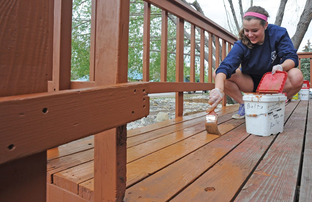 Steamboat Springs High School student Katie Brodie paints a deck at a group home for Horizons Specialized Services in the Riverside neighborhood. Brodie was with a group of students with the National Honor Society who volunteered to help out with the Routt County United Way's Day of Caring on Wednesday.