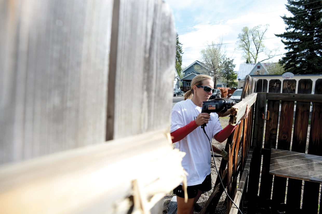 Kara Stoller and a group of volunteers from the Steamboat Springs Chamber Resort Association repair a fence at Integrated Community on Wednesday morning. The project was one of 19 that volunteers tackled as part of the annual Routt County United Way's Day of Caring.