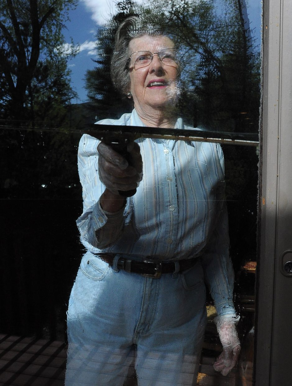 Gloria James, with P.E.O. Sisterhood, cleans a sliding glass door at the Rollingstone Respite House in Steamboat Springs on Wednesday as part of the annual Routt County United Way's Day of Caring.