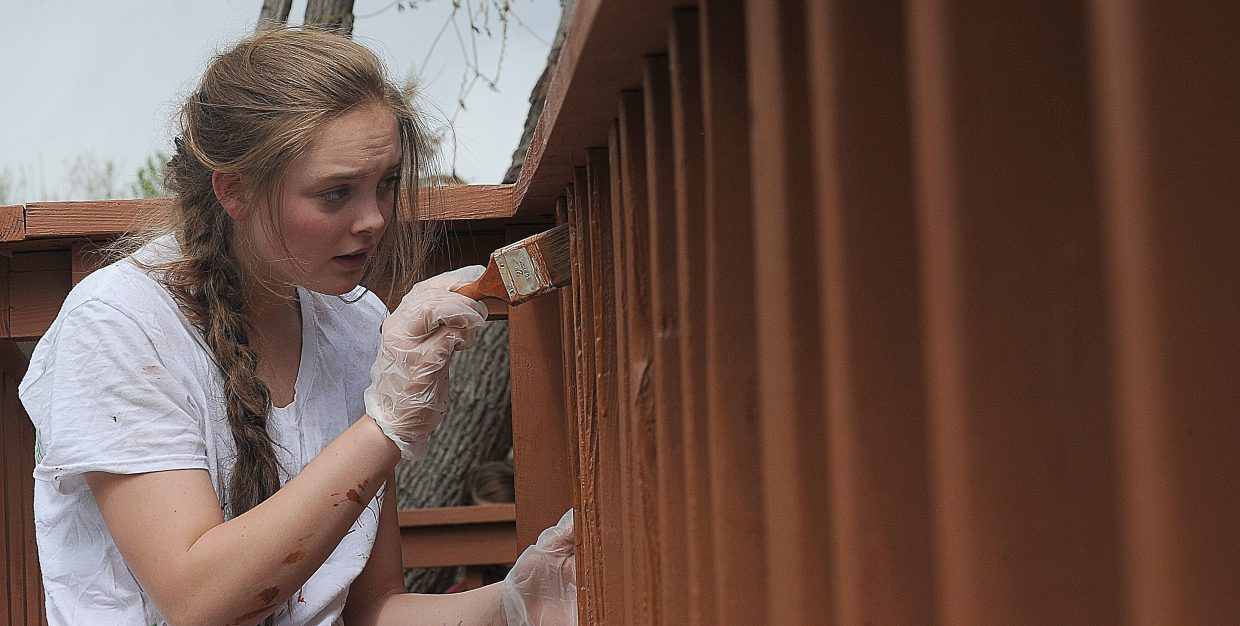 Steamboat Springs High School student Jenna Miller paints a deck at a group home for Horizons Specialized Services in the Riverside neighborhood. Miller was with a group of students with the National Honor Society who volunteered to help out with the Routt Clunty United Way's Day of Caring. Volunteers worked on 19 projects in the Steamboat area Wednesday.