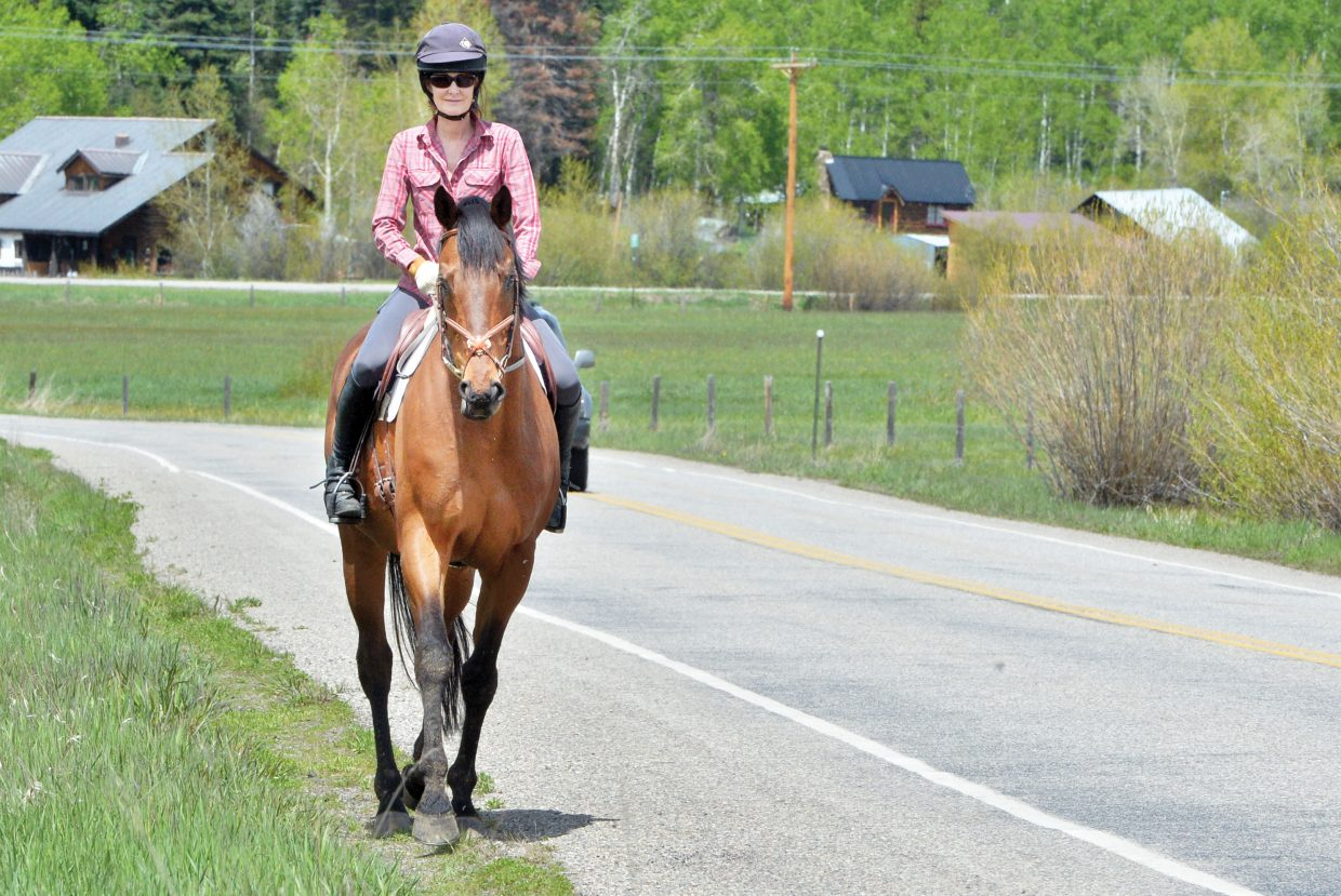 Strawberry Park resident Tania Coffey rides her horse, Quadrant along Amestist Drive on Thursday in search of a dry place to ride. Tania has arranged to use her neightbors dirt road to get the horse out and about after a long streak of rainy weather.