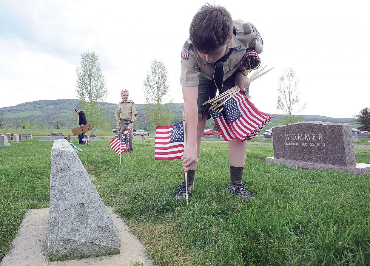 Boy Scout John Slowey, front, and Ryyan Amsden place flags on the graves of Steamboat Springs veterans Thursday evening as part of a Memorial Day tradition for the troop. Steamboat's annual Memorial Day recognition is slated for 11 a.m. Monday. The ceremony is open to the public. Steamboat Springs Transit will provide bus service to the cemetery from the transit center west of town beginning at 9:45 a.m.