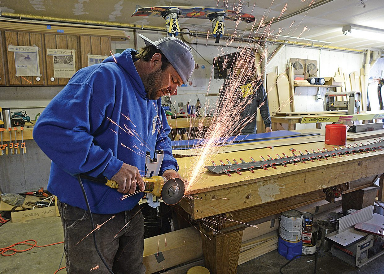 """Clark resident Joe Muhlbauer uses a grinder to cuts a piece of metal used for the edges on his """"Filthy"""" brand skies. Muhlbauer has been creating his own brand of skis and snowboards out of his garage for the past four years and has developed a good local following. A following he is hoping will continue to grow."""