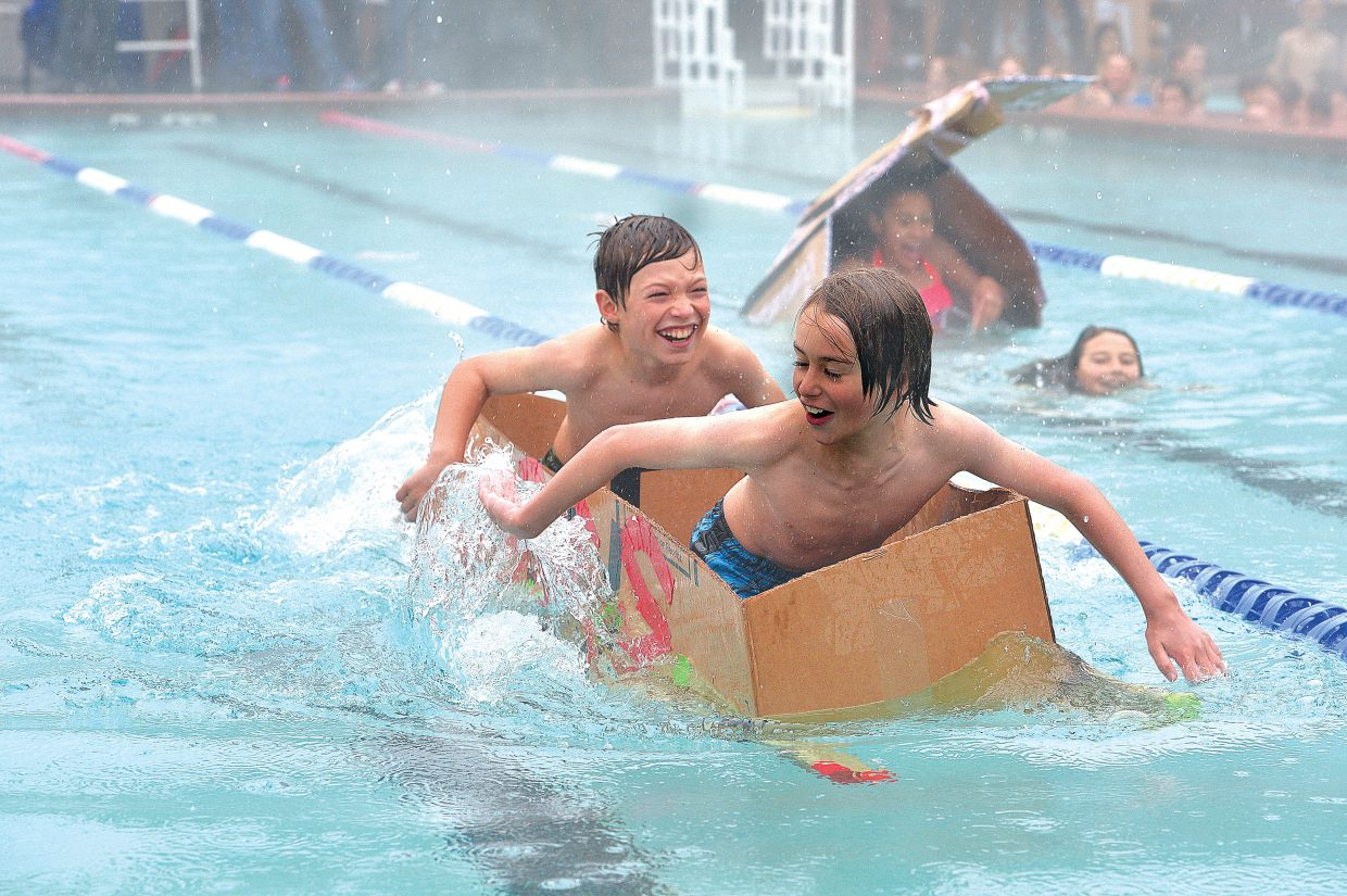 Soda Creek Elementary School fifth-graders Luke Olson and Lukas Znamenacek race across the Old Town Hot Springs pool as part of the 2015 Cardboard Classic. The race was intended to teach the students about design and science, but even in the steady rain, it looked more like fun for the students who took part.