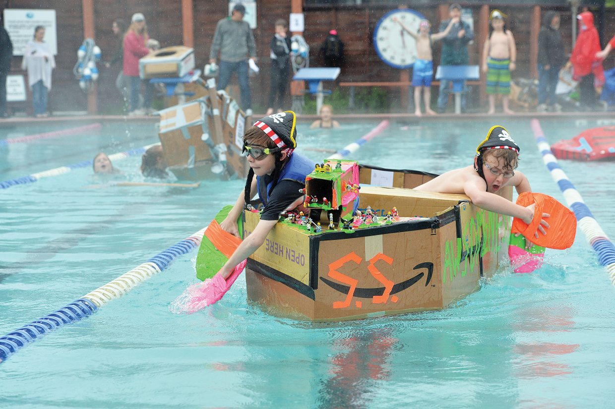 Strawberry Park Elementary School fifth-graders Preston David and Ryan Kitchen race across the Old Town Hot Springs pool as part of the 2015 Cardboard Classic. The race was intended to teach the students about design and science, but even in the steady rain, it looked more like fun for the students who took part.