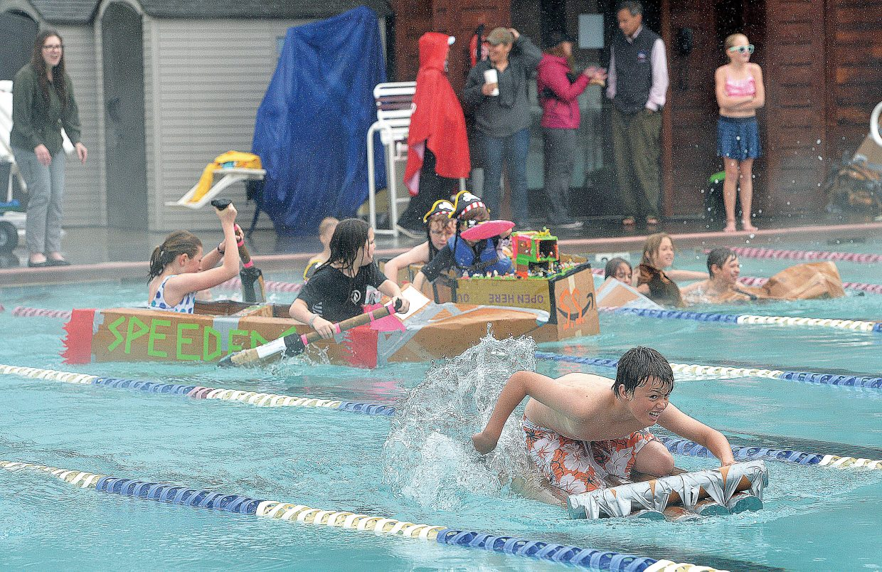 Soda Creek Elementary School fifth-grader Jonathan Rawlings races across the Old Town Hot Springs pool as part of the 2015 Cardboard Classic. The race was intended to teach the students about design and science, but even in the steady rain, it looked more like fun for the students who took part.