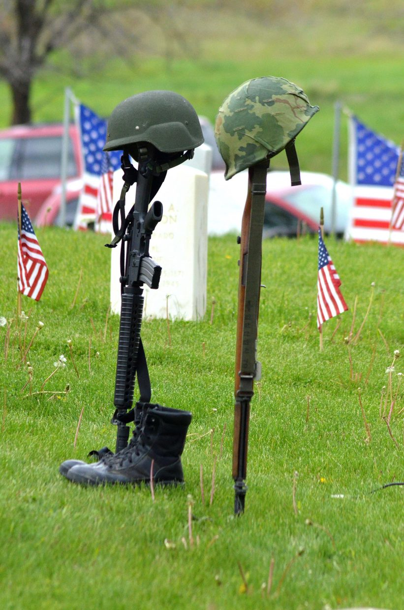 Boots, helmets and rifles sit near white gravestones at Craig Cemetery on Memorial Day.