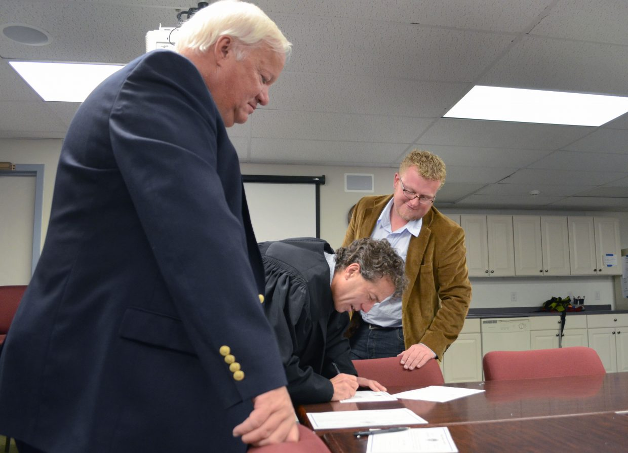 Steamboat Springs Board of Education members Roger Good, left, and Joey Andrew, right, sign oaths of office in 2013.