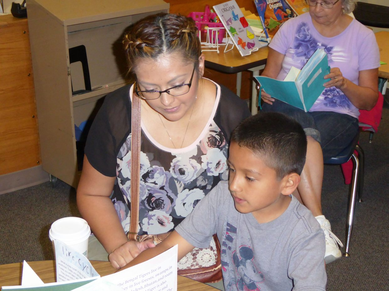 Third-grader Avery Silva reads his book about Bengal tigers to his mother, Jennifer Bernal, on Wednesday at Sunset Elementary School. The reading capped a five-week book-making project for the third-grade students.