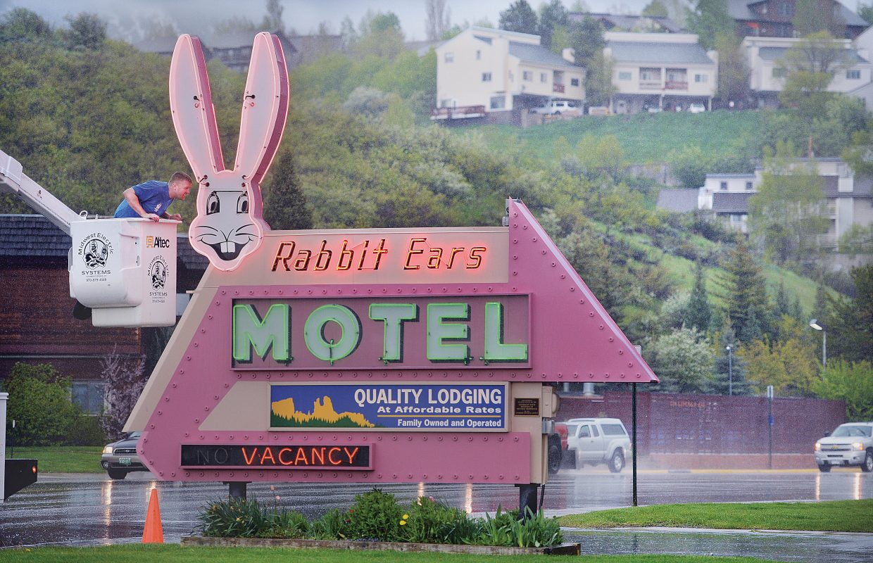 Austin Fox, who works for Midwest Electric Systems, didn't let the steady rain downtown keep him from working on the Rabbit Ears Motel sign. The neon sign that stands on the east side of downtown is a historical landmark that has welcomed visitors to Steamboat Springs for generations.