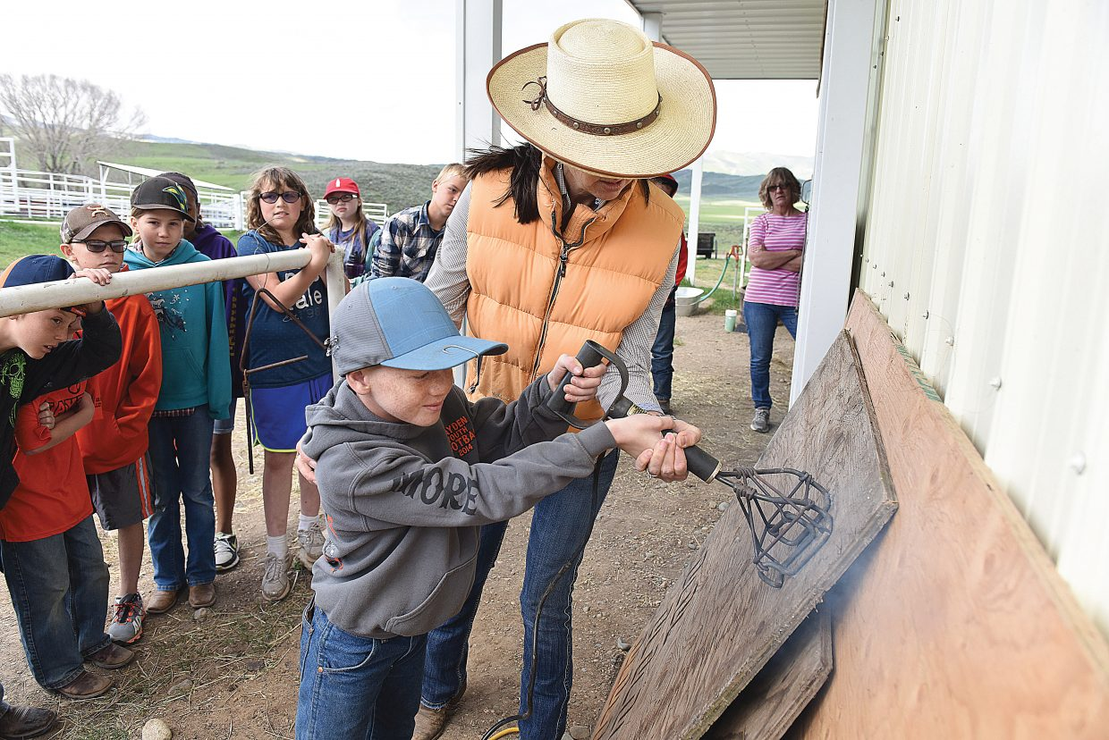 Hayden Elementary School student Kalob More uses a branding iron, with a little help from Coyote Creek Ranch owner Erika Murphy, to leave his mark on a board as part of a demonstration during the 2016 Ranch Days
