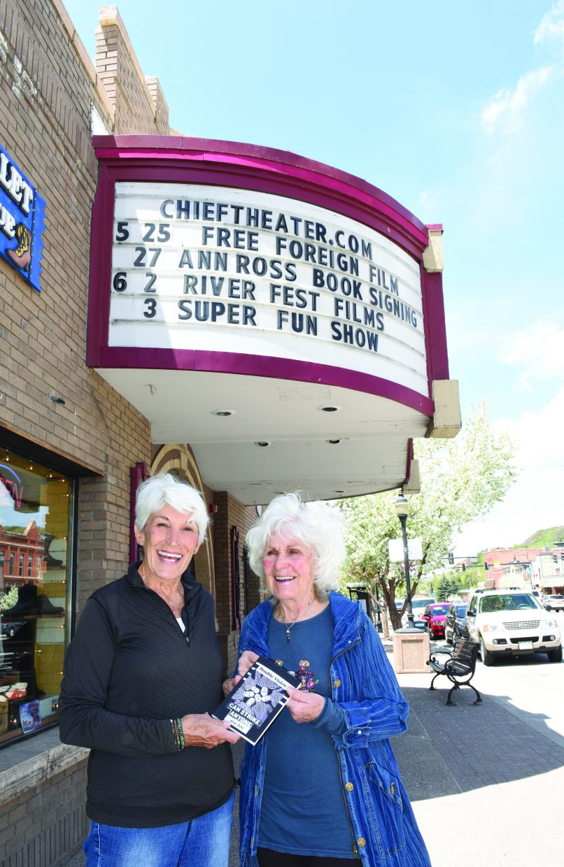 "Local author Ann Ross shares her book with her sister, Carol Saviano, in front of the Chief Theater on Lincoln Avenue. On Friday, Ross will host a book signing for her first book, ""Double Vision."""