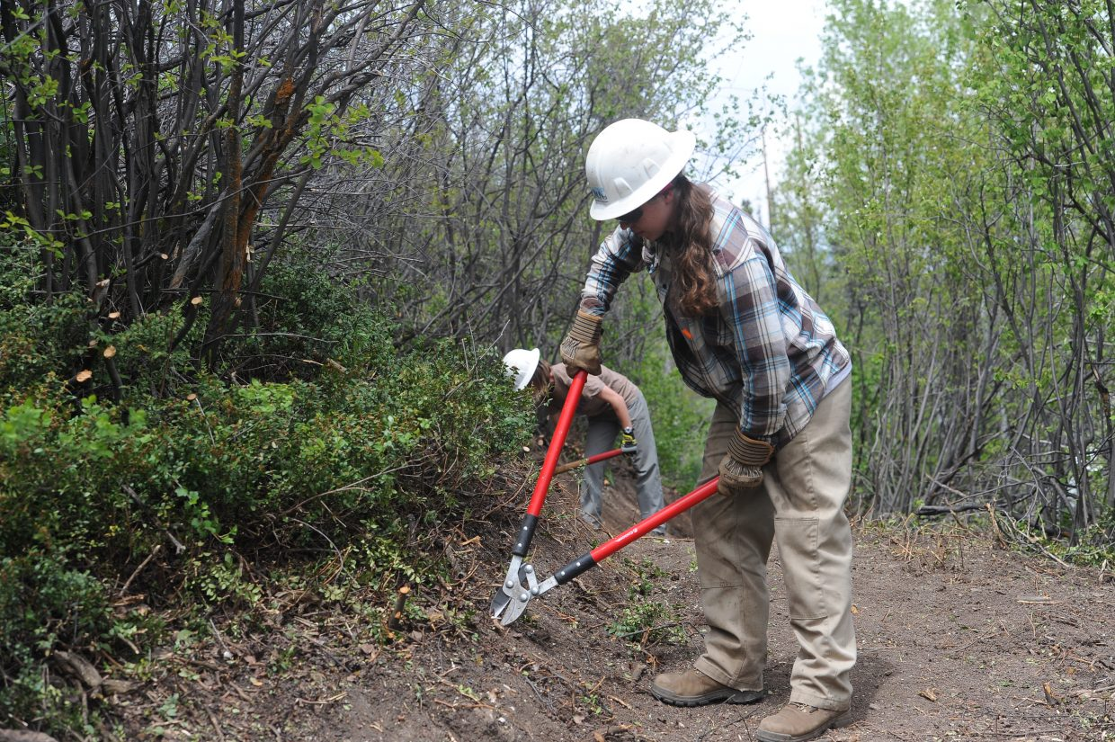 Rocky Mountain Youth Corps crew leader Kassie Nolan works on a portion of the Bluff Loops Trail.