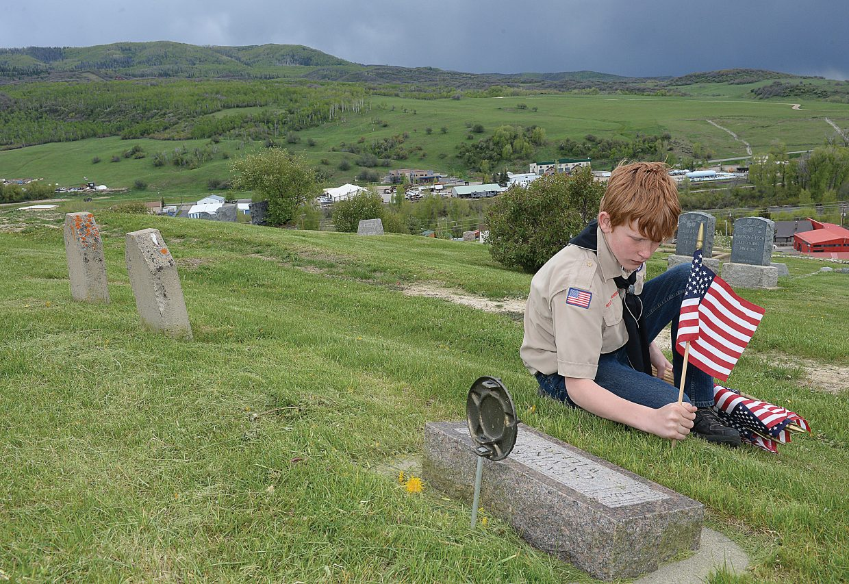 Boy Scout Gabe Harrell places a flag on the grave of a veteran Thursday evening at the Steamboat Springs Cemetery. A ceremony memorializing deceased Steamboat Springs veterans who have served their country begins at 11 a.m. Monday at the Steamboat Springs Cemetery, a tradition in Steamboat since 1920. Steamboat Springs Transit will provide free bus service to and from the ceremony at the Stockbridge Transit Center. The last bus leaves for the cemetery at 10:40 a.m.