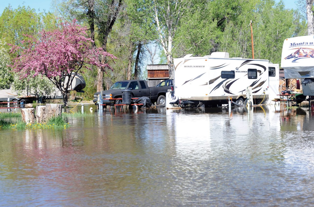 Several inches of water surround campers in the longterm section at the Steamboat Campground in west Steamboat Springs Tuesday morning. The water from the Yampa River has come into the park the past few nights but hasn't really been an issue. The management has offered to allow these campers to move to drier areas, but the owners of the campers elected to stay where they were feeling like the water is on its way back down.