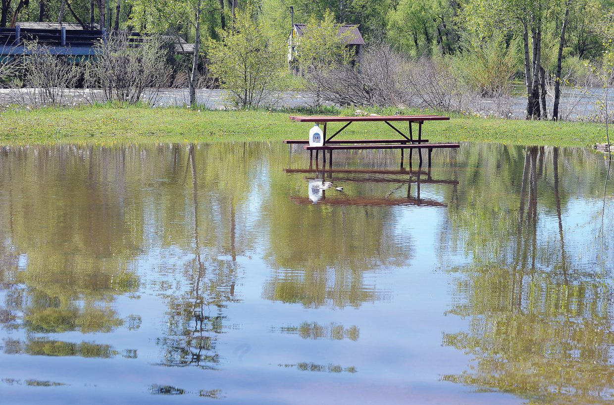 Several inches of water surrounds a picnic table at the Steamboat Camp Ground in west Steamboat Springs Tuesday morning. The water from the Yampa River has come into the park the past few nights, but hasn't really been an issue. The management has offered to allow these campers to move to other areas, but the owners of the campers elected to stay where they were, thinking the water is on its way back down. Flooding at the campground is isolated to a small area near the riverbanks.