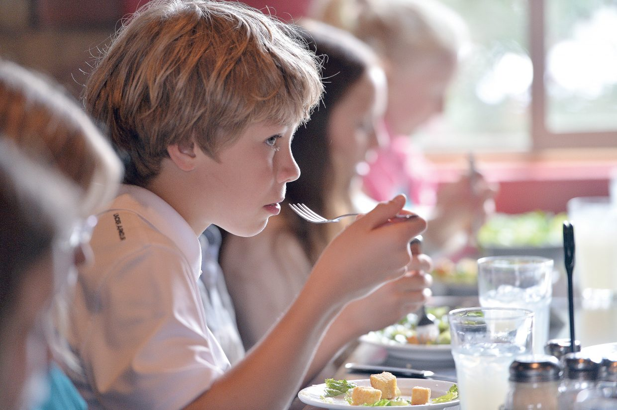 Fifth-grade student AJ Romick listens during a conversation with a classmate while taking part in the formal luncheon Thursday at Mambo Italiano. The luncheon is the culmination of Molly Manners etiquette lessons taught by Molly Hayes. The meal also is a celebration for the children who are making the transition to middle school.