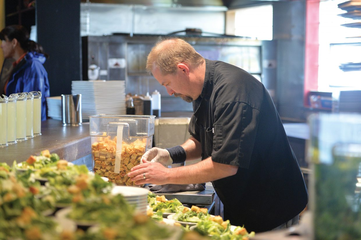 Mambo Italiano employee Dan Bubenheim makes salads for the entire Soda Creek fifth-grade class that was taking part in a formal luncheon Thursday at Mambo Italiano. The luncheon is the culmination of Molly Manners etiquette lessons taught by Molly Hayes. The meal also is a celebration for the children who are making the transition to middle school.
