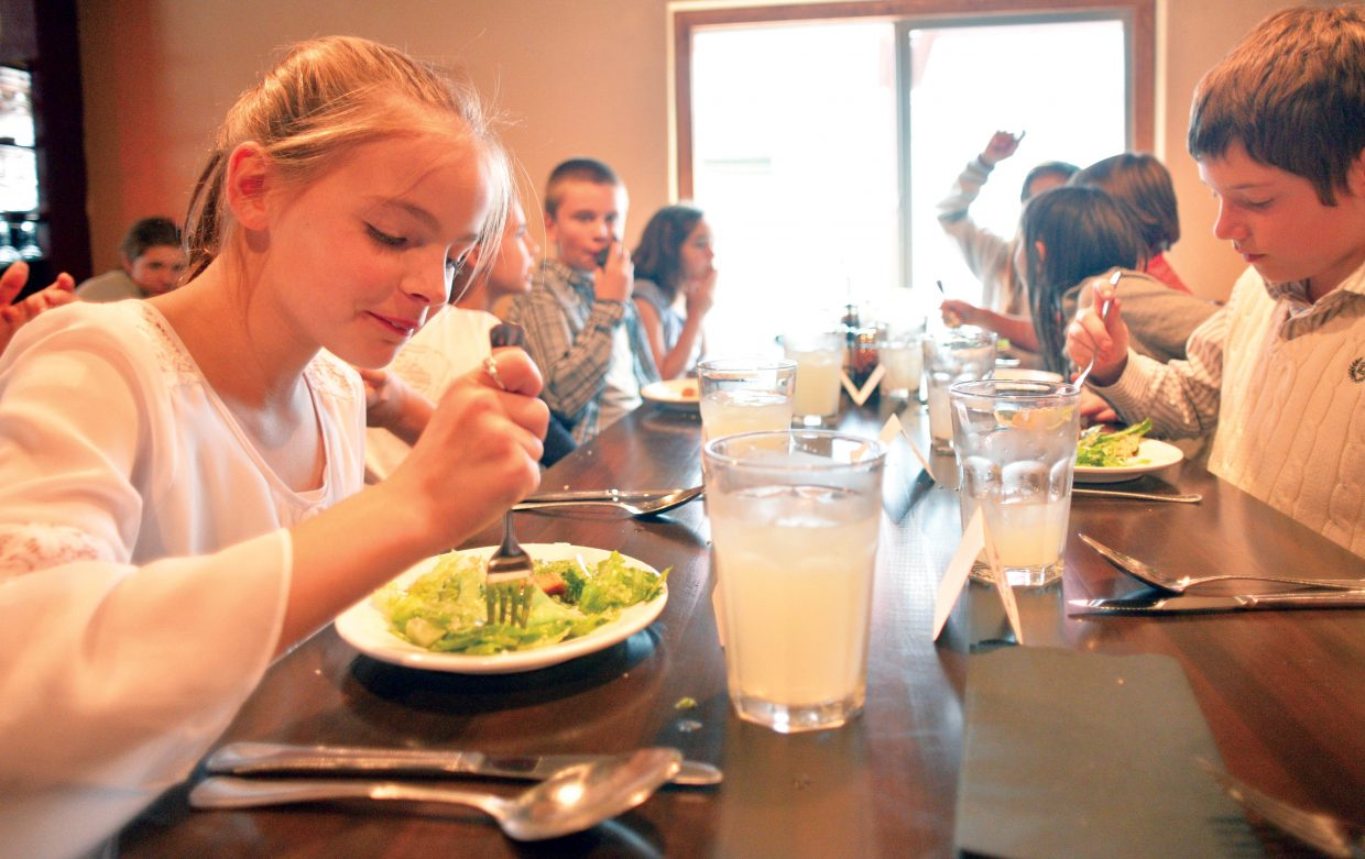 Fifth-grade student Catcher Waynand eats her salad with a classmates during a formal luncheon Thursday at Mambo Italiano. The luncheon is the culmination of Molly Manners etiquette lessons taught by Molly Hayes. The meal also is a celebration for the children who are making the transition to middle school.