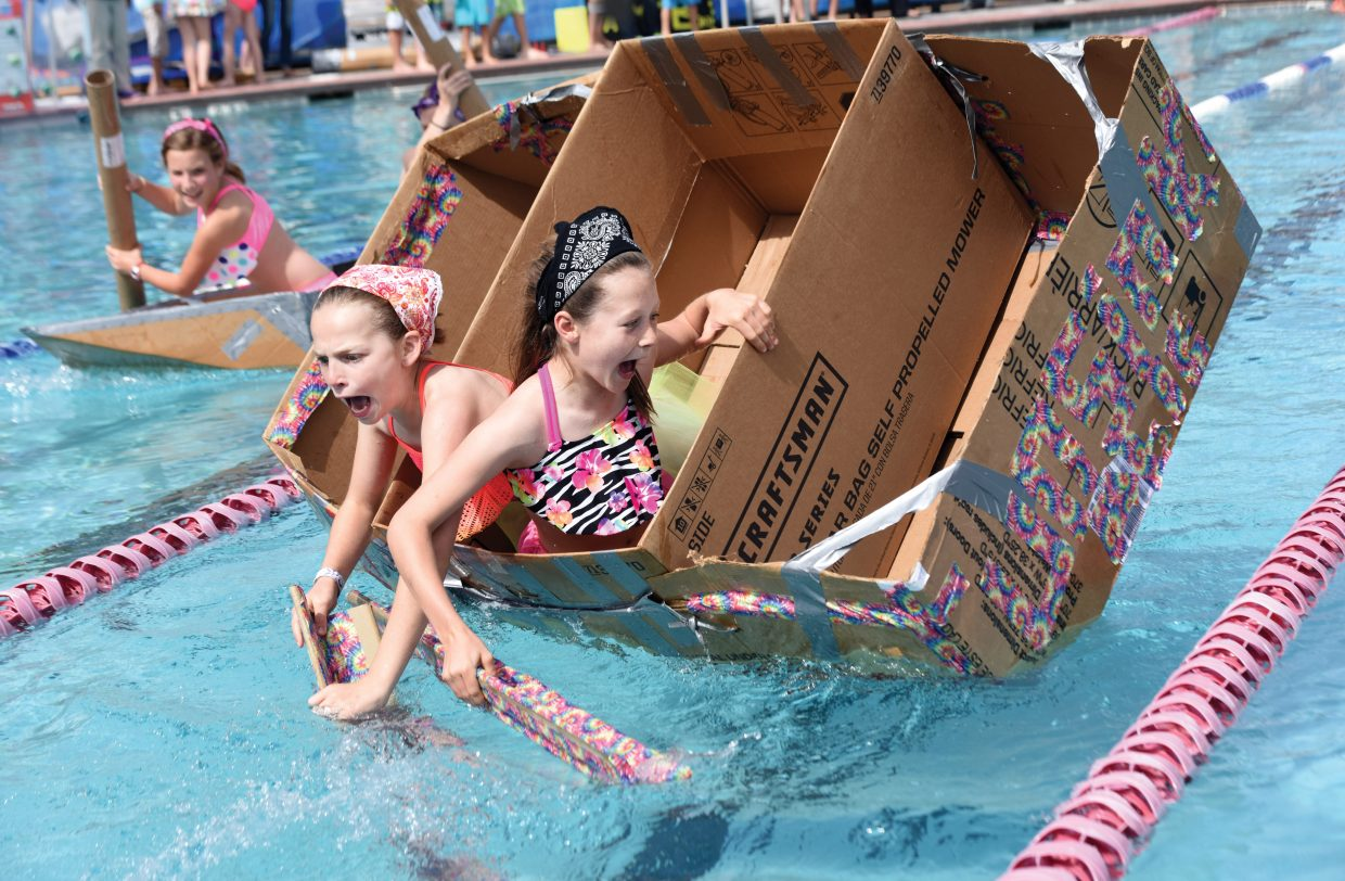 Soda Creek fifth-graders Norah Pietras (front) and Meaghan Maitre bail out of their craft during the annual Cardboard Classic at the Old Town Hot Springs pool Friday. Teams of students built the crafts using only cardboard and duct tape, then tested them in a race across the pool.