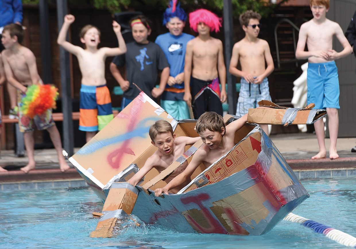Strawberry Park fifth-graders Dawson Holmes (front) and Levi Allen attempt to keep their craft upright as they make their way across the Old Town Hot Springs pool Friday morning as part of the annual Cardboard Classic. Teams of students built the crafts using nothing more than cardboard and duct tape, then tested them in a race across the pool.