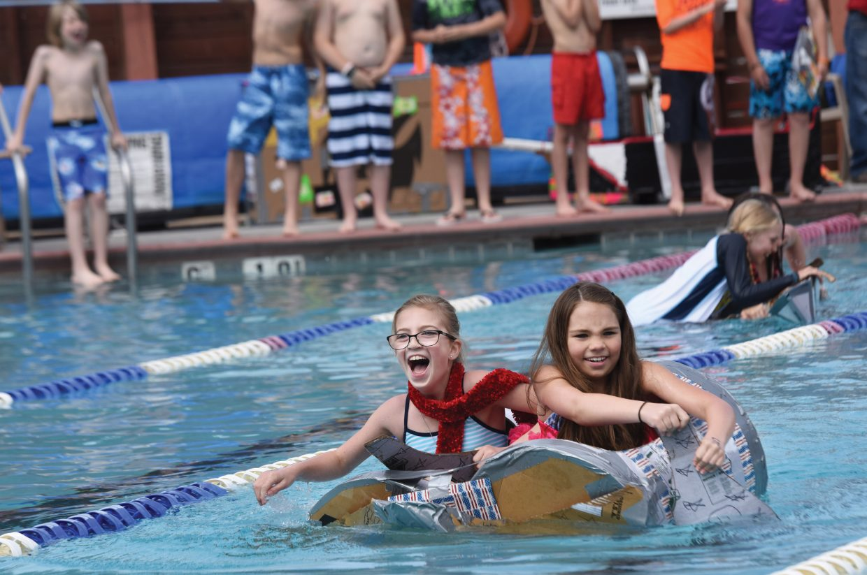 Strawberry Park fifth-graders Haley Creech (left) and Wiley High make their way across the Old Town Hot Springs pool Friday morning as part of the annual Cardboard Classic. Teams of students built the crafts using nothing more than cardboard and duct tape, then tested them in a race across the pool.