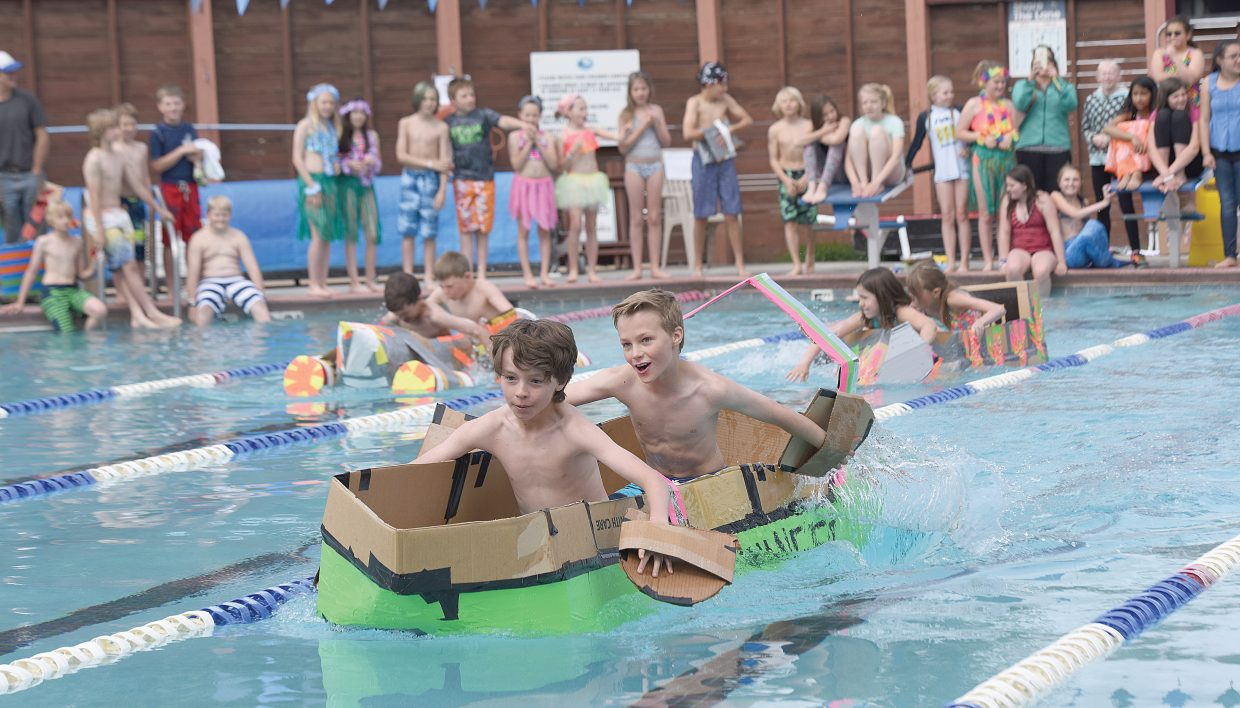 Strawberry Park fifth-graders Fisher St. John (front) and Colin Kagan make their way across the Old Town Hot Springs pool Friday morning as part of the annual Cardboard Classic. Teams of students built the crafts using nothing more than cardboard and duct tape, then tested them in a race across the pool.
