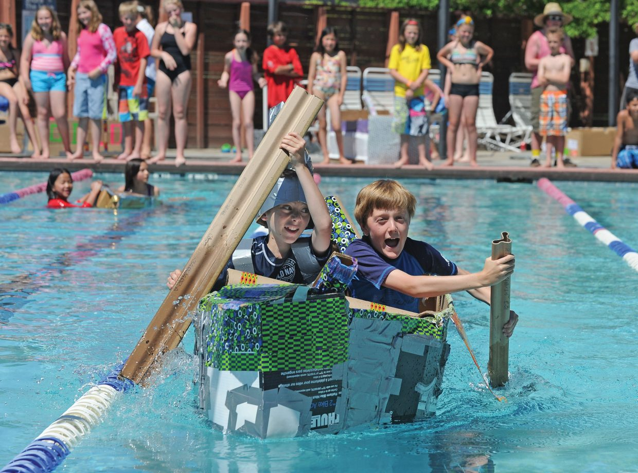 Jaxson Fryer, right, and Anthony Tucciarone paddle their way across the Old Town Hot Springs Pool on Wednesday during the annual Cardboard Classic. The race featured fifth grade students from Soda Creek and Strawberry Park elementary schools who designed, created and raced boats built with cardboard and duct tape.