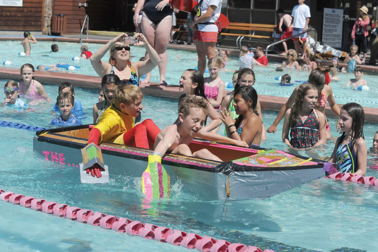 Soda Creek Elementary School fifth-graders Henry Cardillo, front, and Jakob Kreissig paddle for the other side of the pool during the annual Cardboard Classic race Wednesday at the Old Town Hot Springs. The race featured fifth grade students from Soda Creek and Strawberry Park elementary schools who designed, created and raced boats built with nothing more than cardboard and duct tape. The pair won the race along with teammates Tommy Mewborn and Jack Becker.